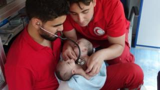 Syrian Arab Red Crescent medics hold conjoined twins Nawras and Moaz before evacuating them from Douma (12 August 2016)
