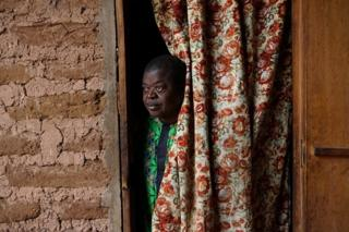 Man looking through a curtain
