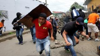 Demonstrators take cover as police fire at them during a protest against the government of Nicaraguan President Daniel Ortega in Masaya, Nicaragua June 19, 2018.