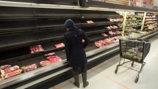 A shopper looks at empty shelves.