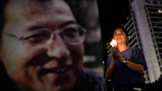 A lady binds a candle as she attends a burial for terminally-ill Nobel laureate Liu Xiaobo (pictured on banner) in Hong Kong on Jun 29, 2017