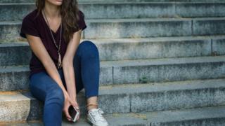 girl sat on steps holding phone