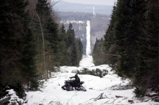U.S. Border Patrol Agent Andrew Mayer rides a ATV as he looks for signs of illegal entry along the boundary marker cut into the forest marking the line between Canadian territory on the right and the United States March 23, 2006 near Beecher Falls, Vermont.
