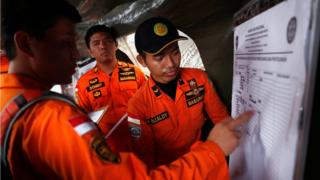 Indonesian rescue teams update a manifest chart