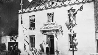 """Guernsey woman standing outside house with a sign saying """"welcome, at long last liberty"""""""