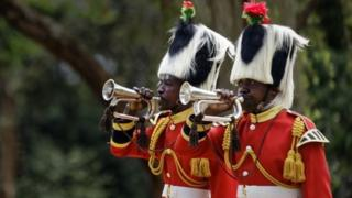 """Members of a Kenyan military band sound bugles to mark the start of two minutes"""" silence on Remembrance Sunday at the Nairobi War Cemetery in Kenya Sunday, Nov. 13, 2016. The annual event is observed in Britain and around the Commonwealth to honor the contribution of those British and Commonwealth military who died in the two World Wars and later conflicts. (AP Photo/Ben Curtis)"""