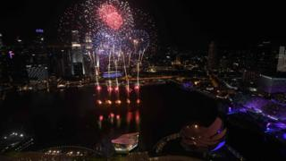 Fireworks burst over the water of Marina Bay during the New Year countdown celebration in Singapore