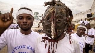 Dos jóvenes combatientes en la población de Kananga, uno de ellos con una máscara tradicional utilizada en ceremonias hechiceras.