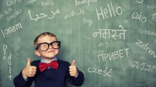 Niño frente a una pizarra con palabras en varios idiomas.