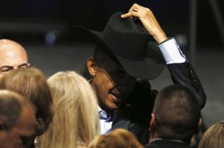 US President Barack Obama tries on a supporter's cowboy hat