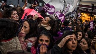 Women's rights activists react during clashes with Turkish riot police as they try to march to Taksim Square to protest against gender violence in Istanbul, on November 25, 2018