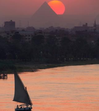 The sun sets over the historical site of the Giza Pyramids and the Nile River, near Cairo, Egypt, Friday, Aug. 19, 2016.