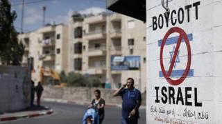 A tourist photographs a sign painted on a wall in the West Bank biblical town of Bethlehem on 5 June 2015, calling to boycott Israeli products coming from Jewish settlements