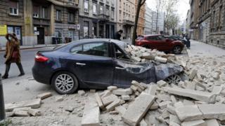 Bir kişi Zagreb, Hırvatistan yakınlarındaki 5,3 büyüklüğündeki bir depremden sonra bir sokakta yatan molozları geçiyor, 22 Mart 2020