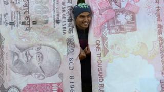 Hombre posando con réplicas de los billetes que cancelaron en India.