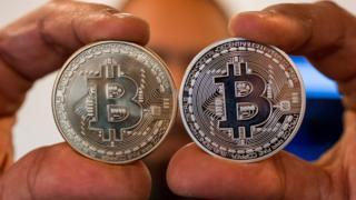 Dos manos sosteniendo un bitcoin cada una.