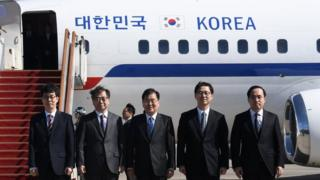 """Chung Eui-yong (C), head of the presidential National Security Office, Suh Hoon (2-L), the chief of the South""""s National Intelligence Service, and other delegates pose before boarding an aircraft as they leave for Pyongyang at a military airport in Seongnam, south of Seoul, South Korea,"""