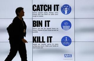 Woman walks past sign displaying public health advice