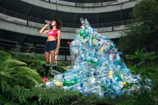 Woman drinking water beside empty bottles