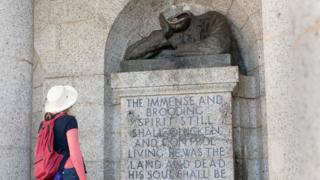 Visitor looks at damaged Rhodes statue