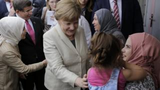 Chancellor Angela Merkel (centre) meeting refugees at a camp in Turkey, 23 Apr 16