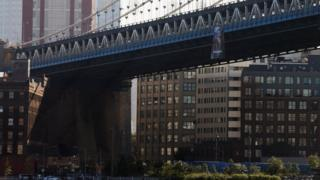 A wide view of the Manhattan bridge, with the banner showing Putin wearing a suit, in front of the Russian flag, with the word 'peacemaker' along the bottom