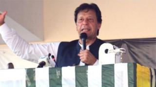 पाक प्रशासित कश्मीर की राजधानी मुज़फ़्फ़राबाद में रैली के दौरान भाषण देते इमरान ख़ान