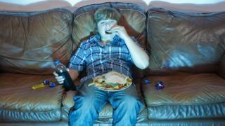 Menino comendo diante da TV
