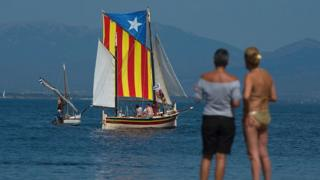 A sail boat carrying an Estelada, the Catalan independence flag, sails off a beach of L'Escala, near Girona on 10 September 2016, on the eve of the National Day of Catalonia, or Diada