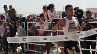 Salah Ameidan crossing the finish line