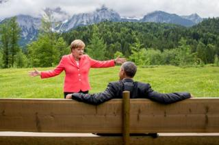 Angela Merkel spreads her arms wide while talking to then US President Barack Obama in June 2015, against a dramatic mountain backdrop in southern Germany.