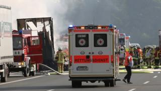 完全に燃え落ちたバスが緊急車両の向こうに見えている(3日)