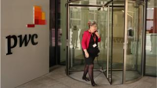 A woman walks into the PwC building in London