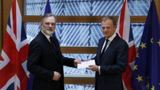 El representante de Reino Unido ante la Unión Europea, Tim Barrow, hace entrega al presidente de la Comisión Europea, Donald Tusk , de la carta formalizando la salida del país del bloque económico.