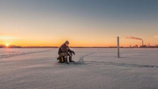 Angler on frozen lake, Estonia
