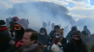 People running away from a cloud of smoke, with sunglasses and scarves over their faces, at a French protest, 28 April 2016