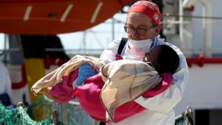 """A doctor carries a child as migrants disembark from the MSF vessel at Pozzallo""""s harbour in Sicily, Italy, 25 April 2016"""