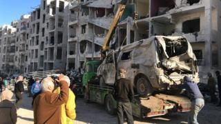 People remove a destroyed vehicle from the scene of an explosion in Idlib city, Syria (8 January 2018)