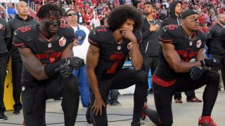 Eli Harold, Colin Kaepernick and Eric Reid kneeling before a match in 2016