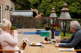 A diver practises at home in the garden as his parents look on