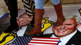 Palestinians walking on a poster of Donald Trump and Vice President Mike Pence in December
