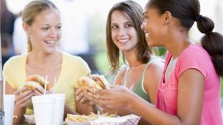Adolescentes comiendo hamburguesas en un restaurante.