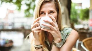 سيدة تركز النظر أمامها وهي تشرب فنجانا من الشاي