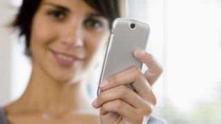 mujer mostrando a la cámara el celular