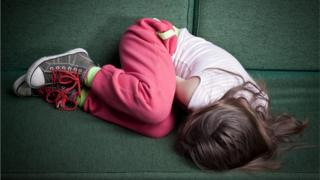 Child in foetal position on sofa.