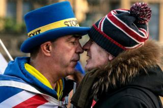 Two men wearing hats stand face-to-face