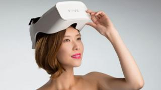 A woman lifting a white virtual reality headset up from her forehead