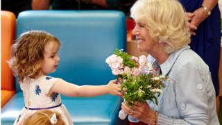 Duchess of Cornwall, is presented flowers from two-year-old Elisabeth Colquhoun in Perth Australia