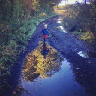 Child about to jump in puddle