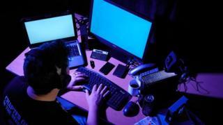 Человек сидит в темной комнате перед экранами двух компьютеров.